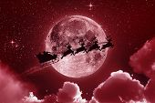 image of stelles  - Santa flying in his sleigh against a full moon background with stars and clouds - JPG