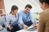 stock photo of rental agreement  - Young couple signing financial contrat on digital tablet - JPG