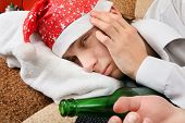stock photo of sad christmas  - Sad and Tired Teenager with Bottle of the Beer and Santa Hat on the Sofa at the Home - JPG