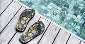 stock photo of thong  - Pair of colorful floral slip slops or thongs left on a wooden deck above a pool at a tropical resort - JPG