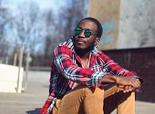 Outdoor Fashion Portrait Of Stylish Young African Man Listens To Music And Enjoys Freedom In The Cit poster