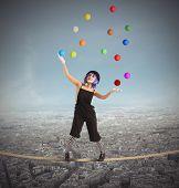 foto of juggler  - Clown as juggler is balancing on rope - JPG