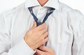 pic of tied  - Man tying his tie over bright shirt close up - JPG