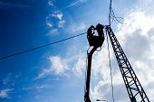 stock photo of pole  - Technician works in a bucket high up on a power pole - JPG