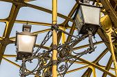 stock photo of spreader  - Decorative lamps hanging from old bridge - JPG