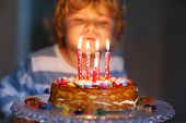 foto of pretty-boy  - Adorable four year old kid celebrating his birthday and blowing candles on homemade baked cake indoor - JPG