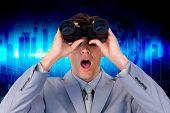 stock photo of binoculars  - Suprised businessman looking through binoculars against blue bar chart graphic with light - JPG
