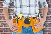 stock photo of crop  - Cropped image of technician with tool belt around waist against red brick wall - JPG