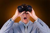 image of binoculars  - Suprised businessman looking through binoculars against orange background with vignette - JPG