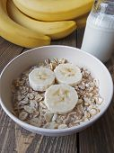 picture of porridge  - oat porridge with bananas and yogurt on a wooden table