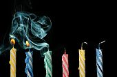stock photo of wind blown  - birthday candles that have just been blown out with smoke on black background - JPG