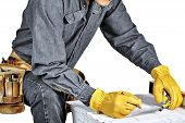 picture of denim wear  - Man in blue denim wearing used tool belt filled with carpenter tools reviewing blueprints holding a tape measure and a pencil - JPG