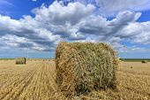 pic of haystack  - round wheat haystack in windmill farm field with white grey clouds on blue sky - JPG
