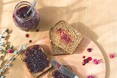 picture of dry fruit  - Fresh baked healthy bread with blackcurrant jam - homemade marmalade with fresh organic fruits from garden. In rustic decoration,dried roses, silver spoon and knife, fruit jam on toasted breadon wooden table background. 