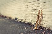 picture of trumpets  - Old worn trumpet stands alone against a grungy pealing white brick wall outside a jazz club - JPG