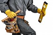 pic of leather tool  - Man in black denim wearing used tool belt filled with carpenter tools carrying a yellow level hardhat and hammer - JPG
