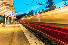 image of commutator  - Summer evening view of high speed commuter passenger train departing from railway station platform with motion blur effect - JPG