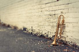 pic of wind instrument  - Old worn trumpet stands alone against a grungy pealing white brick wall outside a jazz club - JPG
