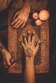 image of haldi  - Drawing process of henna menhdi ornament on woman - JPG