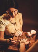 pic of haldi  - Drawing process of henna menhdi ornament on woman - JPG