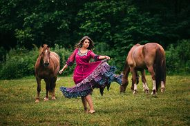 pic of shepherdess  - Beautiful gypsy in violet dress with horses - JPG