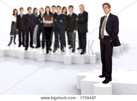 Picture or Photo of Business leadership and teamwork with a businessman in front of a businessteam all standing on puzzle pieces