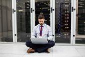 Technician using laptop in server room poster