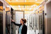 Technician examining server in server room poster