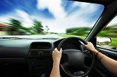 Постер, плакат: Руки на рулевое колесо автомобиля и движения смазывания асфальт и небо