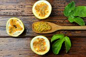 Pulp Of Passion Fruit In The Wooden Spoon Next To Passion Fruit Cut In Half With Leaf On Wooden Tabl poster