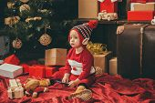 Child With A Christmas Present On Wooden Background. Happy Children. Babies. Winter Kids. Christmas  poster