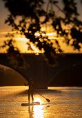SUP Stand up paddle board concept - Pretty, young woman paddle boarding on a lovely lake during warm poster