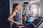 Personal Training With A Trainer On A Treadmill. The Trainer Controls The Correctness Of The Exercis poster