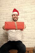 Man Santa Smile And Give Red Wrapped Christmas Present On Wooden Box On White Brick Wall. Gift Givin poster