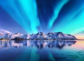 Northern Lights And Snow Covered Mountains In Lofoten Islands, Norway. Aurora Borealis. Starry Sky W poster