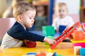 Cute Little Kid Boy Playing With Abacus In Nursery. Preschooler Having Fun With Educational Toy In D poster