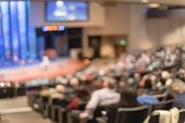 Blurry Background Rear View Audience At Bible Church With Preacher On Stage poster