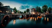 Evening Twilight Panorama Of Amterdam Cityscape With Canal, Bridge And Medieval Houses In The Evenin poster