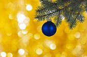 Decoration In The Form Of A Blue Ball With A Glare On The Side Of A Green Christmas Tree And A Blurr poster