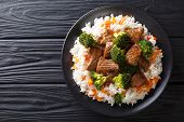 Portion Of Fried Beef With Broccoli With Rice Garnish And Persimmon Close-up On A Plate. Horizontal poster