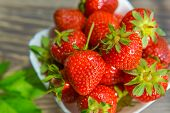 Ripe Red Strawberries. Bowl Filled With Juicy Fresh Ripe Red Strawberries. Strawberries On A Wooden  poster