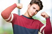 Young handsome man over isolated background showing arms muscles smiling proud. Fitness concept. poster