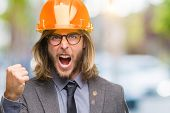 Young handsome architec man with long hair wearing safety helmet over isolated background angry and  poster