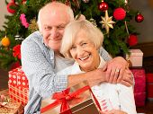 Senior couple with gifts in front of Christmas tree