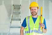 Caucasian Male Contractor With Hard Hat, Level and Safety Vest At Construction Site. poster