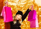 Image of happy cute girl with pink shopping bag, cheerful young lady holding paper presents bags in