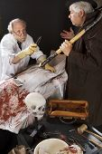 foto of jekyll  - Evil doctor gestures menacingly with knife at grave robber over bloody corpse - JPG