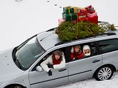 Christmas shopping, celebrating - the family is riding a car with christmas tree and gifts on the ro