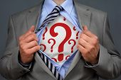 picture of chest  - Businessman in classic superman pose tearing his shirt open to reveal question mark symbol on chest concept for human resources and recruitment - JPG