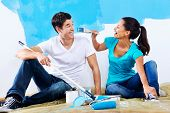 picture of wall painting  - cute couple painting new home together portrait while sitting on wooden floor - JPG